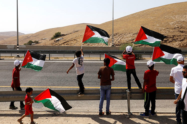 Children wave Palestinian flags on a main road leading from Jerusalem to the Dead sea at the al-Khan al-Ahmar near Jericho in the occupied West Bank on July 4, 2018. Palestinian Preventative Security Forces on July 22 detained Palestinian journalist Huthifa Abu Jamous, according to reports. (Reuters/Ronen Zvulun)
