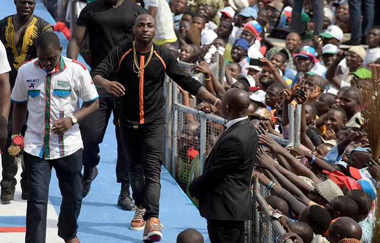 Singer and producer David Adeleke, known as Davido (center) leaves the stage after performing during a political rally in Lagos, Nigeria on January 30, 2015. A member of Davido's private security team assaulted Adekanmbi Damilola, CEO of the online entertainment news platform NoStoryTV, during a concert on July 21, 2018, according to reports. (AFP/Pius Utomi Ekpei)