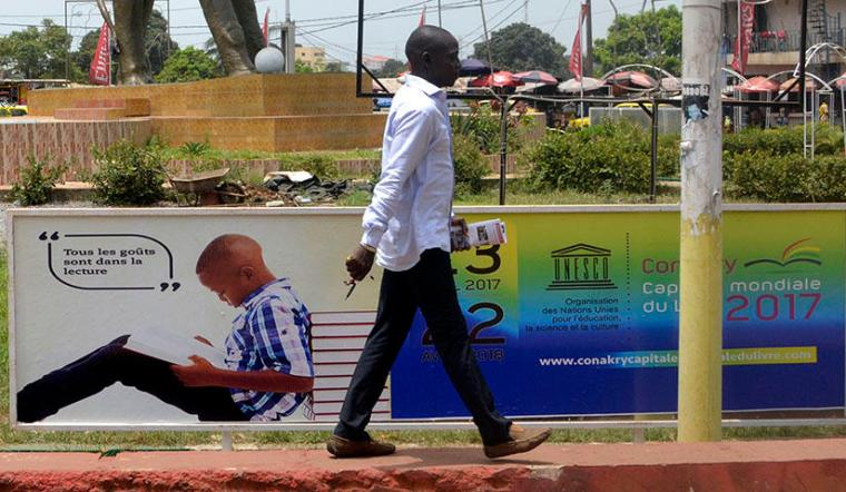 A man walks in Conakry, the capital of Guinea, on April 23, 2017. Guinea authorities arrested journalist Saliou Diallo on June 19, 2018, on defamation charges, according to reports. (AFP/Cellou Binani)