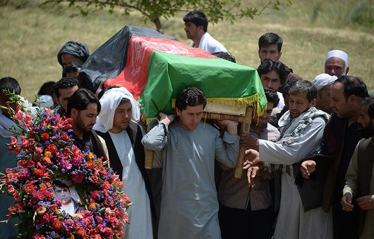 Relatives, colleagues, and friends carry the coffin at a ceremony for AFP driver Mohammad Akhtar in Kabul, Afghanistan, on July 23, 2018, one day after he was killed in a suicide attack in the Afghan capital. (AFP/Noorullah Shirzada)