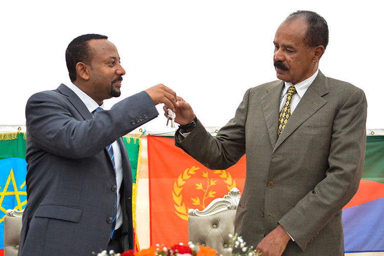 Ethiopian Prime Minister Abiy Ahmed, left, and Eritrean President Isaias Afwerki celebrate the reopening of the Embassy of Eritrea in Addis Ababa on July 16. An Ethiopian news crew was attacked and their driver killed while traveling to the capital to cover the visit. (AFP/Michael Tewelde)