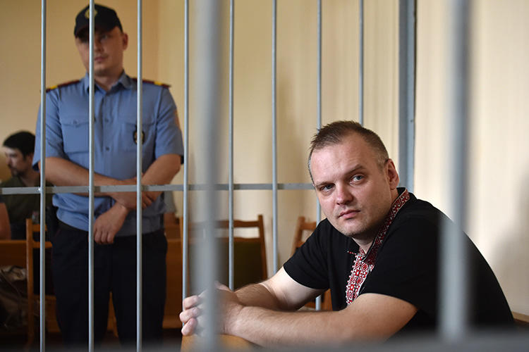 Independent journalist Dzmitry Halko sits in the defendants' cage during his trial in Minsk on July 17, 2018. The court sentenced Halko to four years' detention at a prison colony. (AFP/Sergei Gapon)