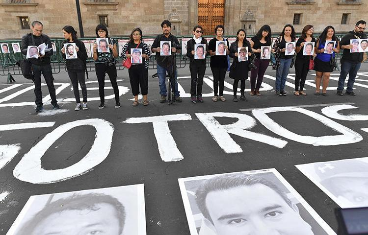 Members of the press hold images of colleagues during a protest against the murder or disappearance of journalists and photojournalists in Mexico, in front of the National Palace in Mexico City on June 1, 2018. Mexican journalist and media owner Rubén Pat was killed in Playa del Carmen, in the southern Mexican state of Quintana Roo, on July 24. (AFP/Yuri Cortez)