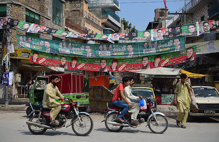 Election posters hang next to a street in Rawalpindi, ahead of elections on July 25. Pakistan's journalists say retaliation against critical reporting is making them self-censor to try to avoid retaliation. (AFP/Farooq Naeem)