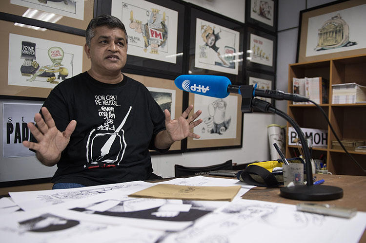 Political cartoonist Zunar, pictured in his Kuala Lumpur office in 2015. A court in Malaysia dropped nine sedition charges against Zunar. (AFP/Mohd Rasfan)