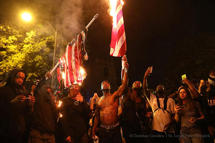 In a photo taken by St. Louis Post-Dispatch photographer Christian Gooden, Black Lives Matter protesters and others burn U.S. flags during a protest in September 2017. Gooden was hit by pepper spray while covering the protests. (Christian Gooden/St. Louis Post-Dispatch)