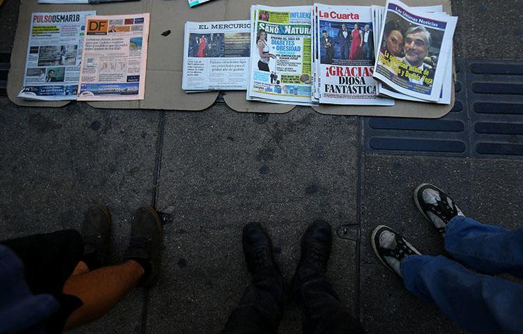 Jornais são vistos na calçada em Santiago, no Chile, em 5 de março de 2018. Um jornalista chileno enfrenta pena de prisão por difamação se for condenado em um julgamento marcado para agosto de 2018. (Reuters/Ivan Alvarado)