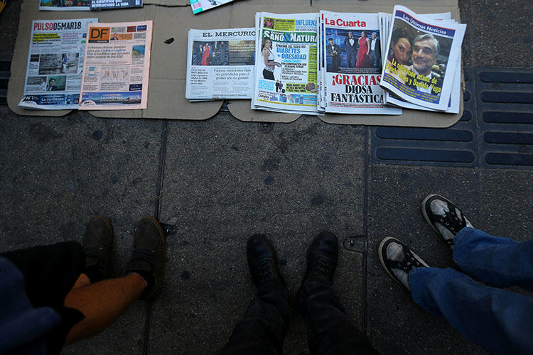Newspapers are seen lying on the pavement in Santiago, Chile, on March 5, 2018. A Chilean journalist is facing jail time on criminal defamation charges if convicted in a court date set for August 2018. (Reuters/Ivan Alvarado)