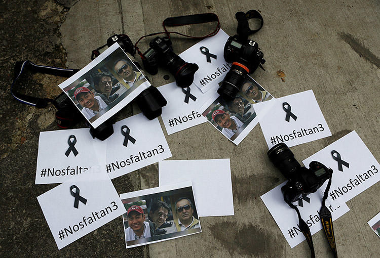 Colombian photographers leave cameras and photos outside the Ecuadoran embassy to protest the killing of journalist Javier Ortega, photographer Paul Rivas, and their driver Efrain Segarra. (Reuters/Jaime Saldarriaga)