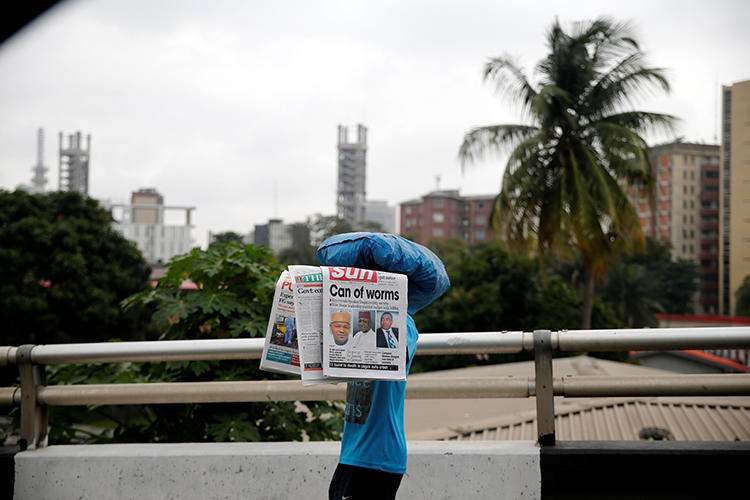 A vendor carrying newspapers walks past on a bridge in Lagos on July 22, 2016. The Nigerian Broadcasting Commission closed the Broadcasting Service of Ekiti State on July 14, 2018. (Reuters/Akintunde Akinleye)