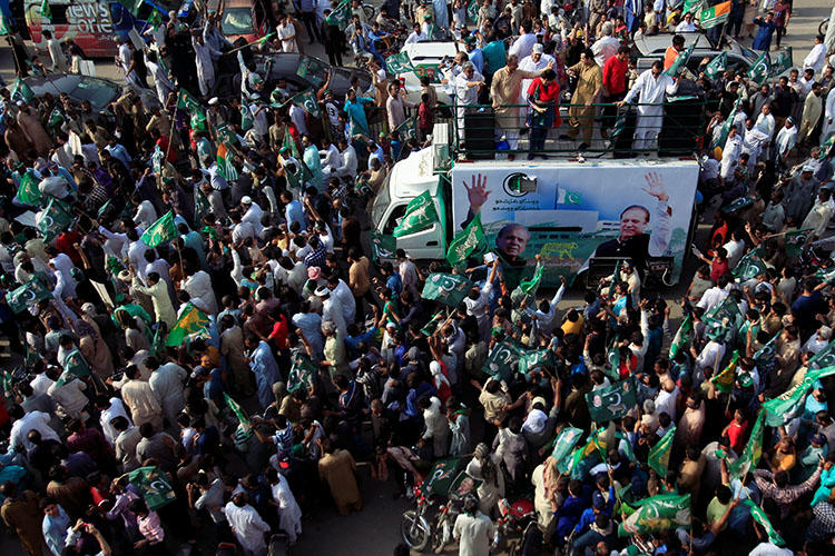 Supporters of the Pakistan Muslim League-Nawaz march toward the airport to welcome former Prime Minister Nawaz Sharif, in Lahore, Pakistan, on July 13, 2018. Pakistani police arrested and beat a Norwegian TV reporter covering a Sharif rally in Gujrat on July 13. (Reuters/Mohsin Raza)