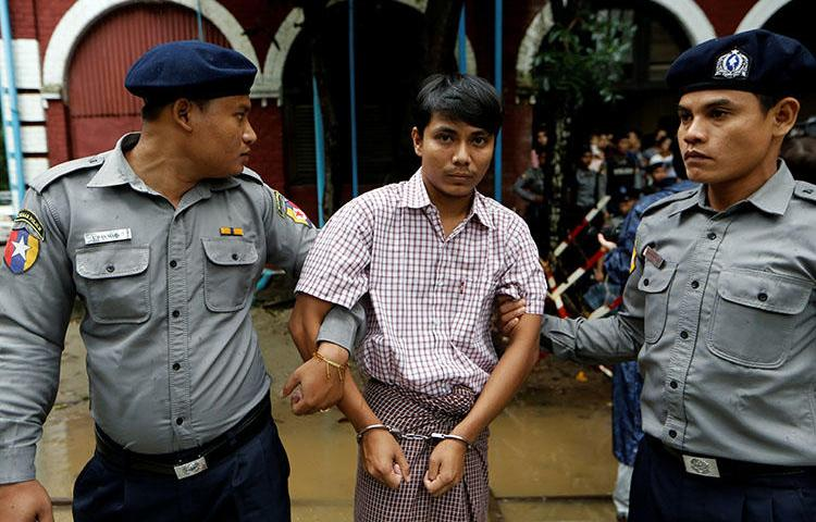 Detained Reuters journalist Kyaw Soe Oo is escorted by police while leaving Insein court in Yangon, Myanmar on July 9, 2018. (Reuters/Ann Wang)