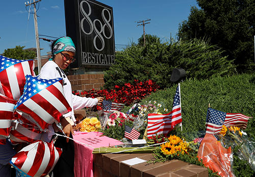 A resident lays an American flag at a memorial outside the Capital Gazette offices. (Reuters/Leah Millis)