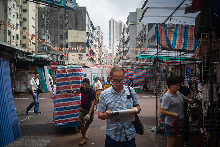 A man reads a newspaper while walking through a market in Hong Kong in May 2018. The Hong Kong Journalists Association says press freedom in the administrative region is in decline. (AFP/Anthony Wallace)