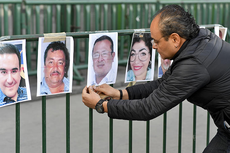 A member of the press hangs pictures of colleagues during a protest against the murder or disappearance of journalists in Mexico in front of the National Palace in Mexico City on June 1, 2018. Mexican cameraman Javier Enrique Rodríguez Valladares was killed in Cancún, in the southern state of Quintana Roo, on August 29. (AFP/Yuri Cortez)