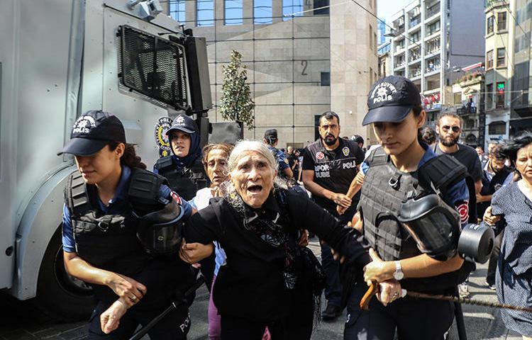 Riot police detain Emine Ocak, a member of Saturday Mothers group, during a demonstration on August 25, 2018, in Istanbul. Turkish police assaulted reporters at the August 25 protest. (AFP/Hayri Tunc)