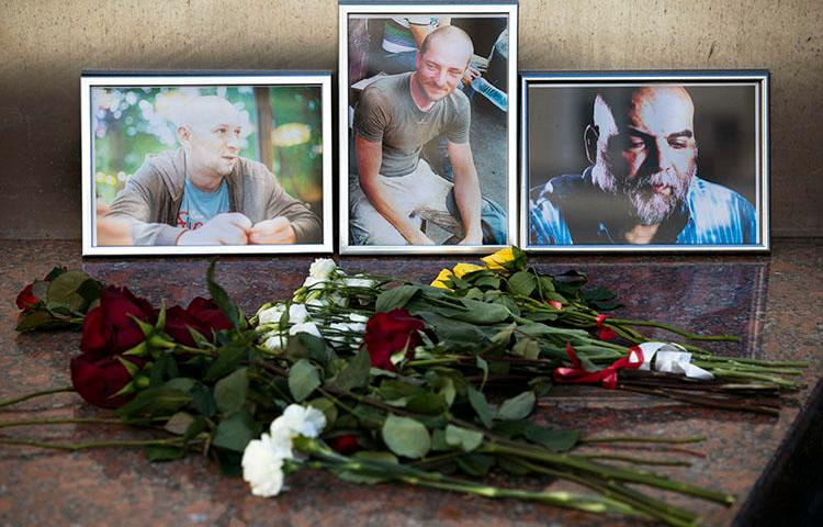 Flowers and photos of Aleksandr Rastorguyev, Kirill Radchenko, and Orkhan Dzhemal are left at the journalist union building in Moscow. The Russian journalists were killed while on assignment in the Central African Republic. (AP/Pavel Golovkin)