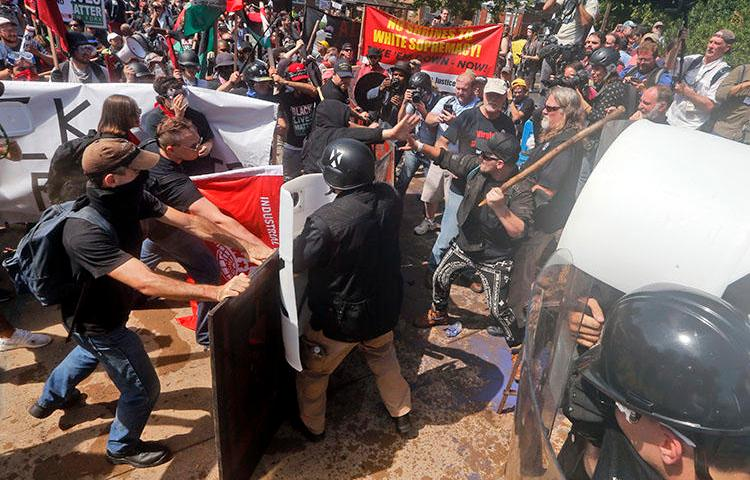 White nationalist demonstrators clash with counter-demonstrators at the entrance to Lee Park in Charlottesville, Virginia, on August 12, 2017. A Unite the Right rally is planned in Washington, D.C., on the one-year anniversary of the Charlottesville demonstrations. (AP Photo/Steve Helber)