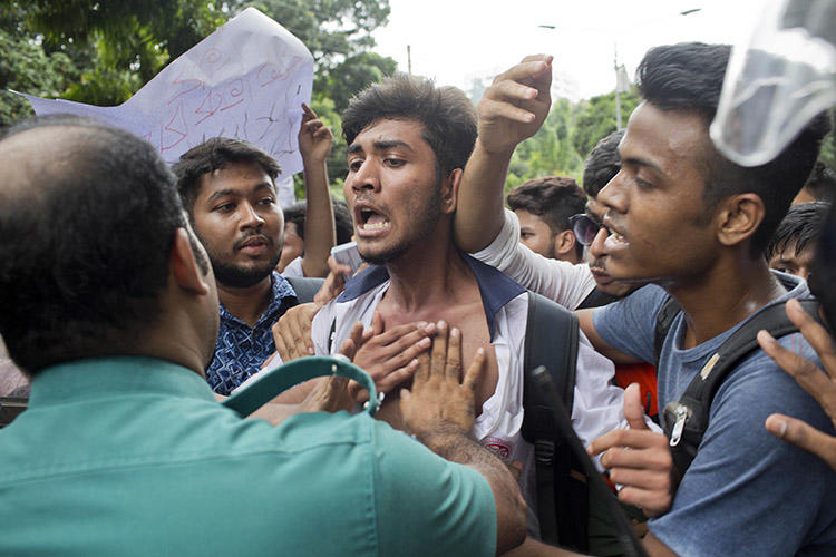 Bangladeshi students attempt to break a police barricade during a protest in Dhaka on August 1. More than a dozen journalists have been attacked covering the nationwide protests. (AP/A. M. Ahad)