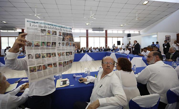 Durante un diálogo nacional con el presidente Daniel Ortega en mayo de 2018, una mujer sostiene un periódico que muestra imágenes de personas que murieron en las protestas en Nicaragua. Más medios de comunicación están ofreciendo noticias contundentes sobre la represión violenta. (AP / Alfredo Zuniga)