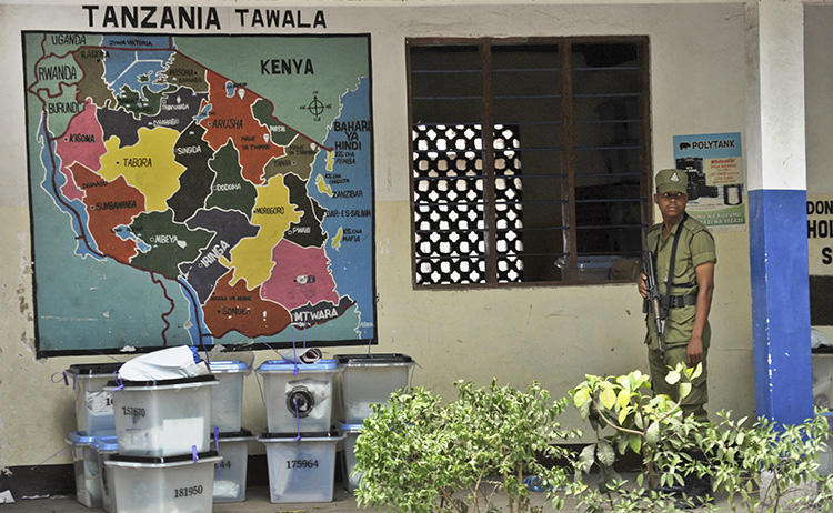 Tanzanian police stand guard outside a vote counting center at a school in Dar es Salaam, Tanzania, on October 28, 2015. On August 16, 2018, CPJ joined a call for the UN Human Rights Council to address a crackdown on free expression and other rights in Tanzania. (AP Photo/Khalfan Said)