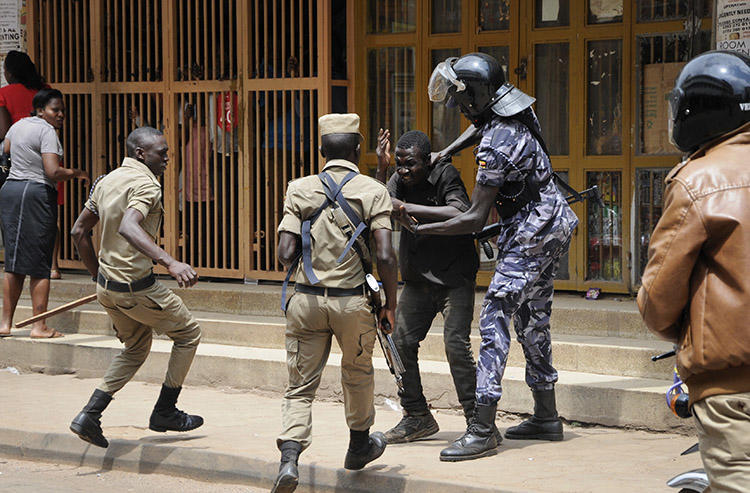 Security forces detain a protester in Kampala on August 20. Security personnel beat and detained at least four journalists who were covering unrest in Uganda's capital. (AP/Ronald Kabuubi)