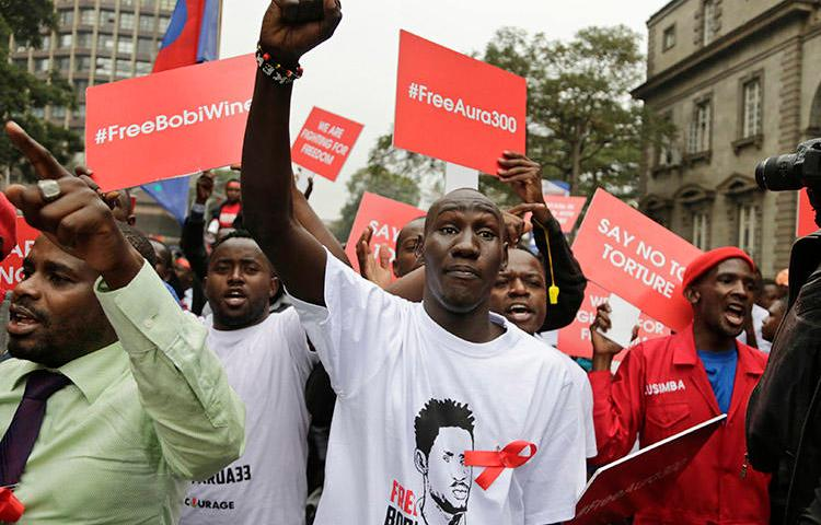 Supporters of a jailed Ugandan lawmaker known as Bobi Wine protest outside the country's embassy in Nairobi, Kenya, on August 23. A Ugandan radio show host was detained overnight after his show broadcast a discussion on the lawmaker's arrest and recent protests. (AP/Khalil Senosi)
