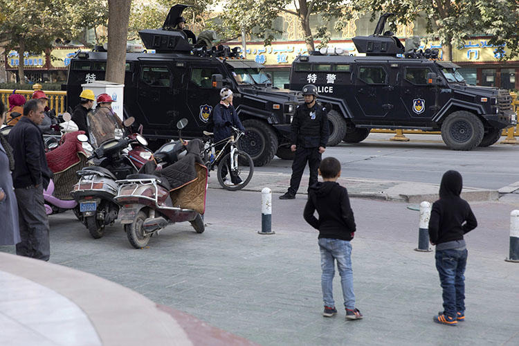 Residents watch a convoy of security personnel and armored vehicles in a show of force through central Kashgar in western China's Xinjiang region in November 2017. China declined to renew the visa of a BuzzFeed journalist who reported on alleged human rights violations in the region. (AP/Ng Han Guan)