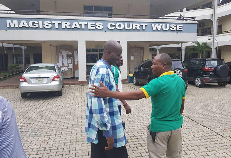 Jones Abiri, left, pictured leaving a court appearance in Abuja on August 2, 2018. The journalist has been detained for two years. (Ahmad Salkida)