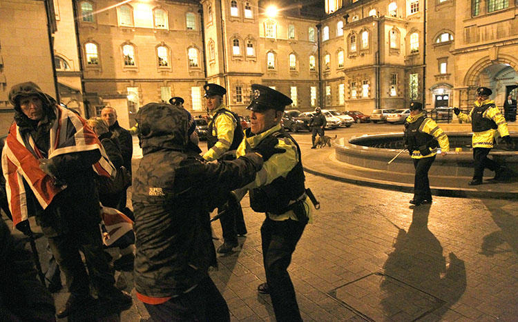 Police Service of Northern Ireland officers confront U.K. loyalists as they try to force their way into Belfast City Hall in 2012. Police arrested two journalists in relation to allegedly stolen confidential documents about a 1994 massacre. (AP/Peter Morrison)