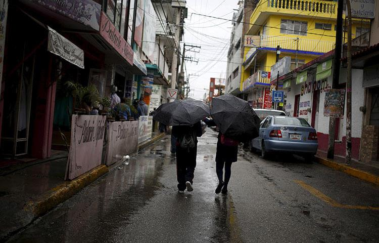 Two people walking in downtown Chilpancingo, in the Mexican state of Guerrero in September 2015. The office of Mexico's Federal Attorney General (PGR) on July 11, 2018, sent an email to the news website Quadratin summoning one of its reporters, Jorge Octavio Vargas Sandoval, for an interview at its regional office in Chilpancingo. (Reuters/Jorge Dan Lopez)