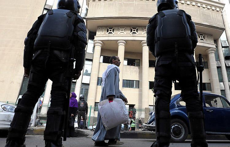 Egyptian security forces stand guard outside a Cairo court during a high-profile trial in January 2018. Prosecutors in August ordered four journalists to be detained on charges of false news and belonging to a banned group. (Reuters/Mohamed Abd El Ghany)