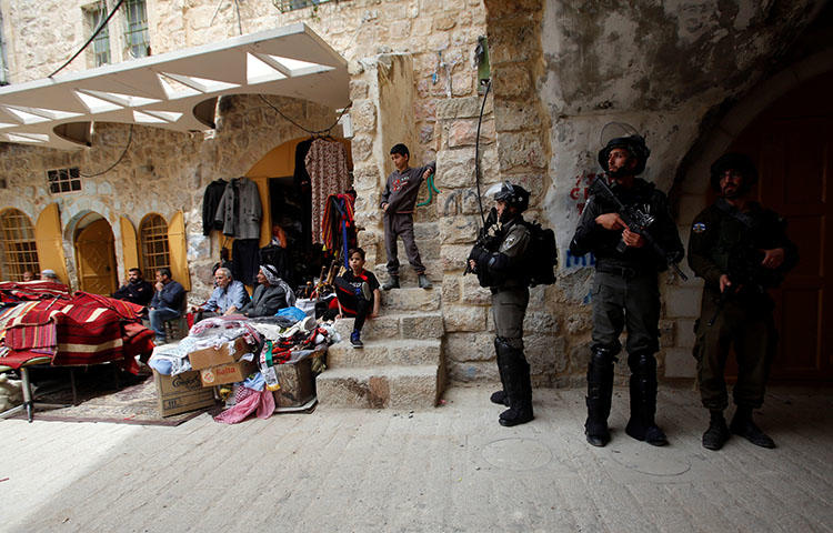 Israeli forces stand guard as Palestinians sit outside shops in Hebron, in the West Bank on April 3, 2018. At least seven Palestinian journalists have been arrested since July 31, according to news report. (Reuters/Mussa Qawasma)
