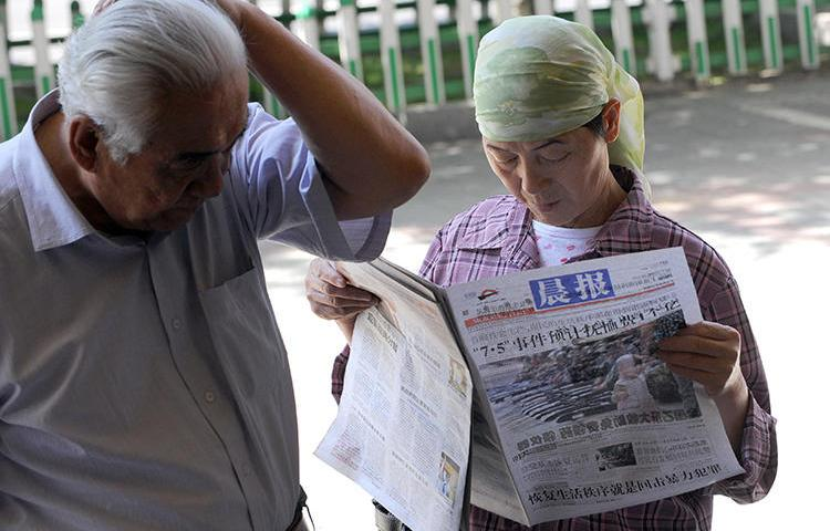 A Chinese Muslim woman reads a newspaper along a street in Urumqi, in China's Xinjiang region, on July 9, 2009. China arrested a Uighur editor and newspaper directors for being 'two-faced' in July and August 2018. (AFP Photo/Goh Chai Hin)