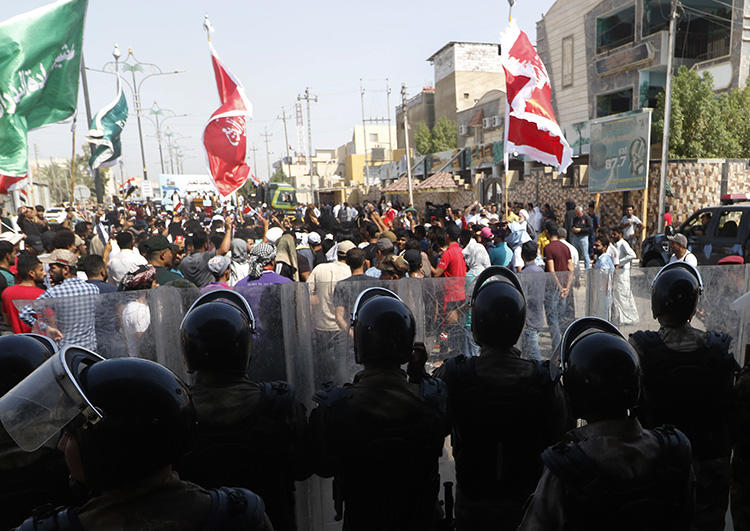 Iraqis shout slogans as security forces form a human barrier during ongoing protests in the southern city of Basra on August 5, 2018. Between July 14 and September 6, 2018, at least seven Iraqi journalists were assaulted or detained while covering protests, and the offices of two local media outlets were set on fire. (AFP/Haidar Mohammed Ali)