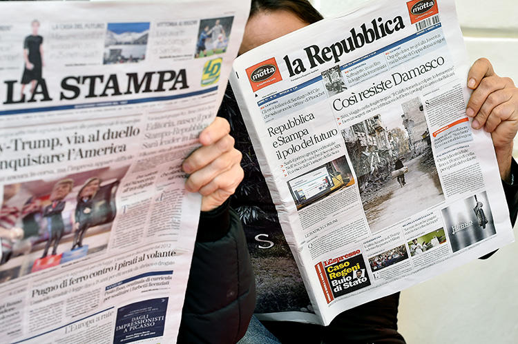 Customers read Italian dailies La Repubblica and La Stampa in Rome on March 3, 2016. Italian police searched a La Repubblica journalist's home and seized electronic devices on September 13, 2018, in Palermo. (AFP/Gabriel Bouys)