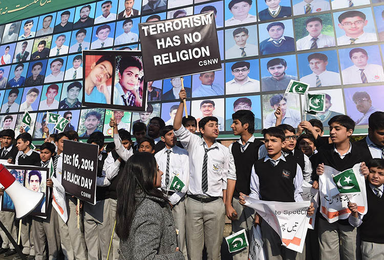 Students and activists gather by images of the victims of the 2014 Peshawar school massacre. A military crackdown after the attack helped reduce violence against the press, but increased self-censorship, journalists say. (AFP/Arif Ali)