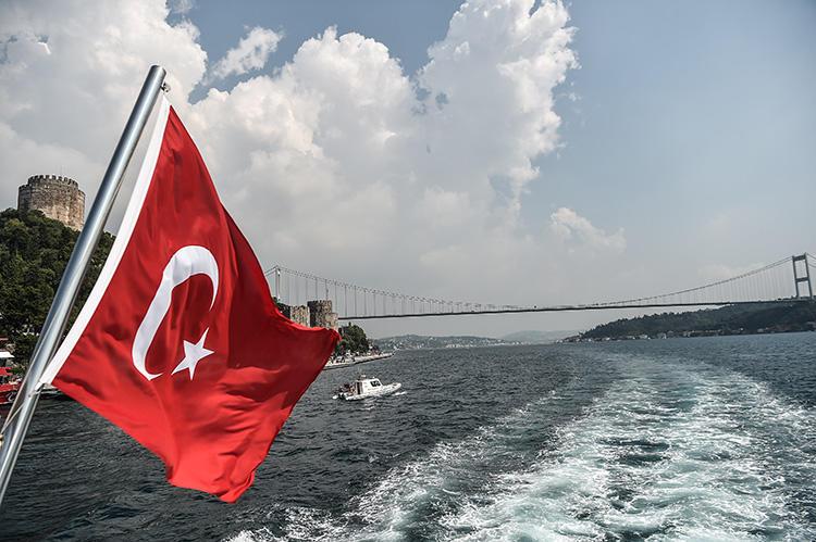 A Turkish flag waves over the Bosphorus strait as Fatih Sultan Mehmet Bridge is seen in the background, on July 22, 2018, in Istanbul. (AFP/Ozan Kose)