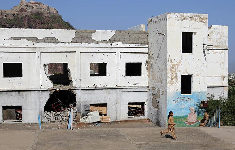 A Yemeni student runs on September 16, 2018, at a school that was damaged last year in an airstrike during fighting between Saudi-backed military coalition forces and Houthis in the city of Taiz. A Saudi airstrike hit a Houthi-controlled radio station in Hodeida Governorate on September 16, killing three employees. (AFP/Ahmad al-Basha)