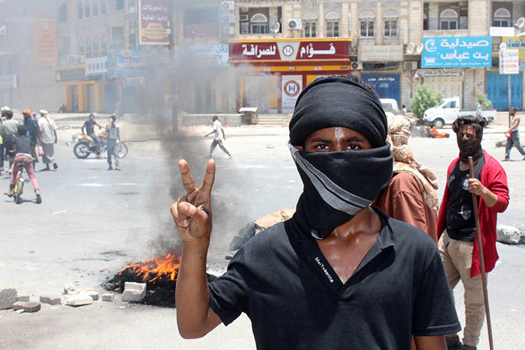 A Yemeni flashes a victory sign during protests in Aden on September 5. Yemeni journalists covering the militias and coalition forces vying for power in the country say they face threats from all sides. (AFP/Saleh al-Obeidi)