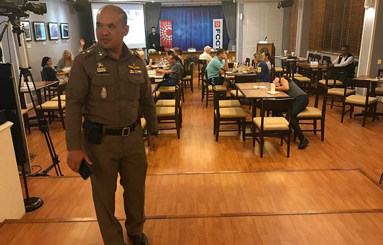 A Thai policeman stands inside the Foreign Correspondents' Club of Thailand on September 10, 2018, during a forum to discuss alleged human rights abuses by the military junta in Myanmar. The discussion was shut down by the Thai authorities. (AP Photo/Tassanee Vejpongsa)