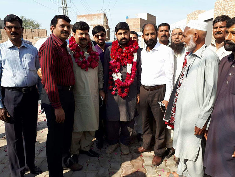 Authorities detained Hafiz Husnain Raza, pictured center in garland, for nearly two years before dropping all charges. The reporter covered land disputes between farmers and the military. (Hassan Raza)