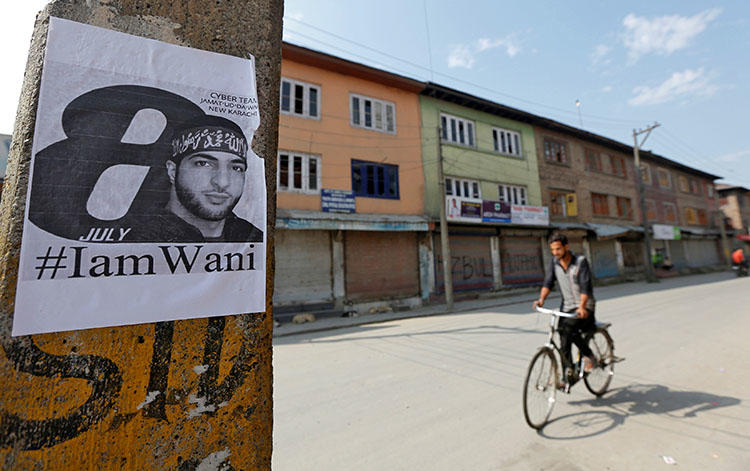 A man rides his bicycle in Srinagar past a poster of Burhan Wani, a commander of the Hizbul Mujahideen militant group who was killed in 2016. Kashmiri authorities arrested and questioned a journalist after he wrote a cover story on the commander. (Reuters/Danish Ismail)
