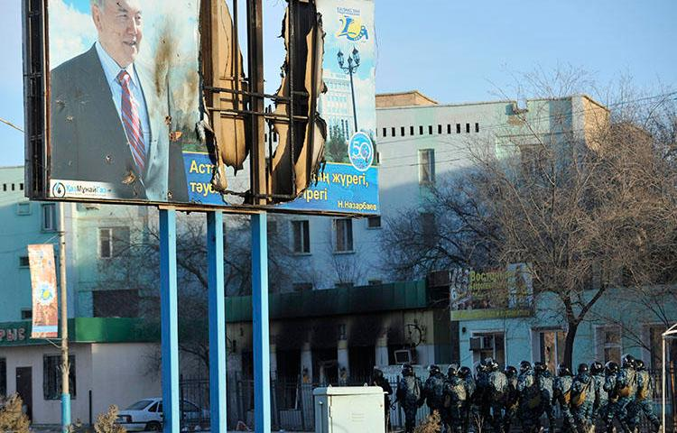 Kazakh Interior Ministry troops patrol beneath a poster of President Nursultan Nazarbayev and partially burnt buildings in Zhanaozen, in December 2011, that were damaged in riots. Kazakh police detained a French journalists today while he interviewed witnesses to the 2011 violence. (Reuters/Vladimir Tretyakov)