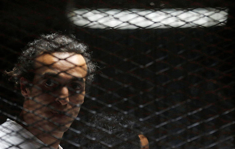Egyptian photojournalist Mahmoud Abou Zeid, also known as Shawkan, looks on behind bars in his trial on the outskirts of Cairo, Egypt, on May 31, 2016. Shawkan was sentenced to five years in prison on September 8, 2018. (Reuters/Amr Abdallah Dalsh)
