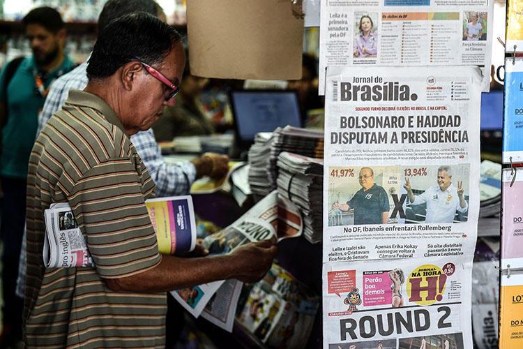 Homem em uma banca em Brasília, em 8 de outubro, lê sobre o primeiro turno das eleições no Brasil. O CPJ e outros grupos de direitos humanos estão pedindo aos candidatos que denunciem ameaças à imprensa. (AFP / Evaristo SA)