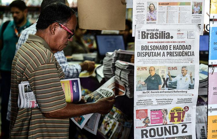 A man at a news kiosk in Brasilia on October 8 reads about the first round of Brazil's elections. CPJ and other rights groups are calling on candidates to denounce threats being made toward the press. (AFP/Evaristo SA)
