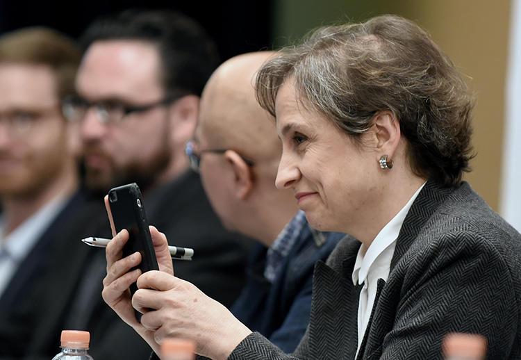 A jornalista mexicana Carmen Aristegui segura seu celular durante uma coletiva de imprensa na Cidade do México em 2017 sobre os governos que usam spyware para atacar jornalistas. (AFP/Alfredo Estrella)