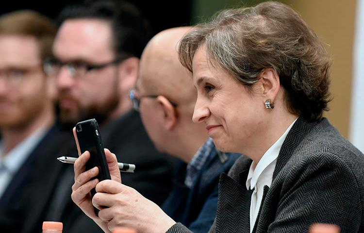 Mexican journalist Carmen Aristegui holds her mobile phone during a press conference in Mexico City in 2017 about governments using spyware to target journalist. (AFP/Alfredo Estrella)