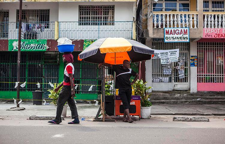 A man stands by a street stall as another one walks past him in Kinshasa, Democratic Republic of the Congo, on December 21, 2016. A newspaper editor was detained for criminal defamation in Kinshasa on October 10, 2018. (AFP/Eduardo Soteras)